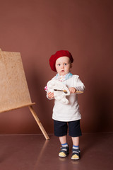 little boy artist brush and paints paints a picture