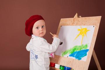 little boy artist brush and paints paints a picture
