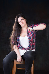 Plus size white female with long dark hair in a casual style on a dark background at a photo studio banging chest with knuckle