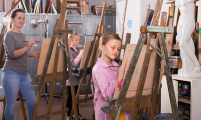 schoolgirls diligently training their painting skills during class at art studio