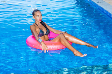 Sexy sporty woman in sensual bikini swimsuit sit in big pink inflatable ring at the pool at hotel resort. Modern urban hipster girl with long fit legs have fun. Good sunny summer day for swim.