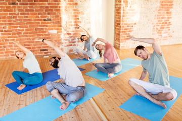 group of people doing yoga exercises at studio