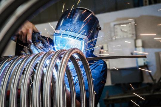 Worker is welding metal tubes.