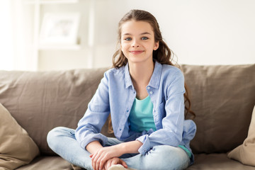 happy smiling preteen girl sitting on sofa at home