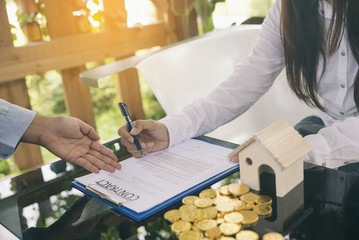 Save money to buy home,sign contract,mortgage concept.Golden coin and model house with boke background.Financial bank officer is pointing at woman to sign a home trading (mortgage) contract.