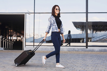 Young woman walking with luggage suitcase, vacations, travel and active lifestyle concept