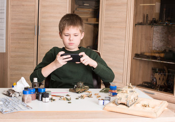 Hobby and leisure concept. Teen boy with smartphone taking picture of plastic model tank which he is assembling and painting at workplace in his room.