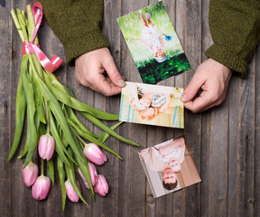 Memories concept, mother's day. Family photos in man hands and on weathered wooden table and bunch of pink tulips. Top view.