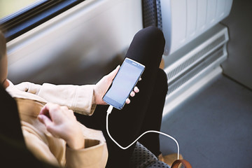 Female hands using mobile phone in train