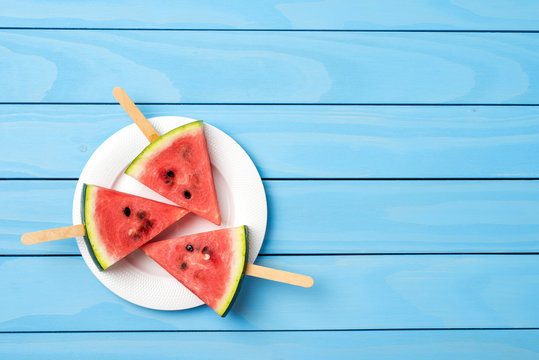Watermelon slices on blue wooden table. Food background