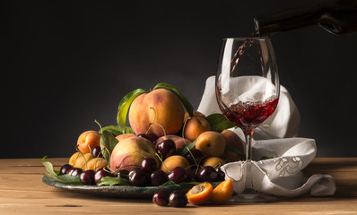 glass with red wine and tray with fruits