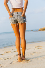 Close up of legs of beautiful fit woman in white shirt and jeans shorts walking away by the beach. Lady hold hands in back pocket. Beauty sunshine cute girl on a tropical sand beach with large stones.