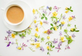 Cup of coffee with milk on the background of small flowers and leaves. Cute simple background. Floral backdrop for banners, cards, covers. The theme of the beginning of the day, summer, spring.