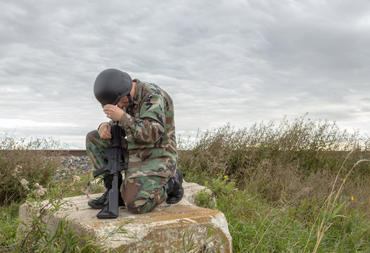 horizontal image of a soldier kneeling down on a big boulder with his gun and his head down saying a prayer.