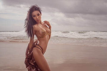 Sensual and elegant brunette beauty wearing gold jewelry bra, black bikini bottom and sarong posing on the beach over amazing sea and cloudy sky background