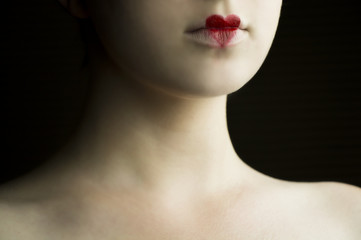 Close up of a young girl's face with red heart drawn on her lips with dark background