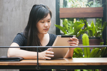Asian young woman working on digital tablet at coffee cafe, work life integration concept