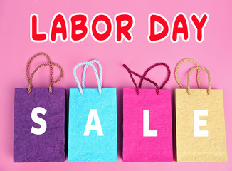 Paper shopping bags on pink background