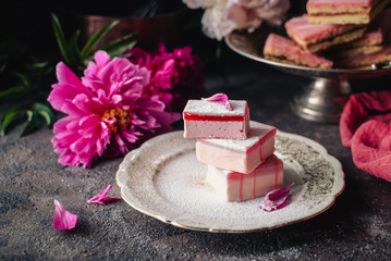 Fruit cakes taffy (lucum) and sand cakes on a dark background, decorated with peonies. Summer light and delicious dessert. Close up