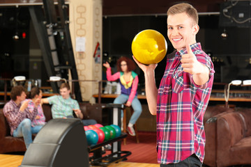 Young man having fun and playing bowling