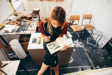 Female artist drawing pictures in her workshop