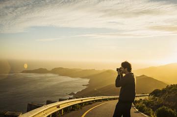 USA, California, San Francisco, California, Silhouette of man photographing coastline at sunset