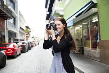 Smiling woman taking picture with camera while standing at outdoors