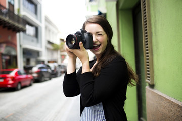 Puerto Rico, San Juan, Woman standing on street and photographing
