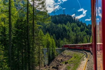 Red train slowly climbing to the Bernina Pass in the Swiss Alps - 4