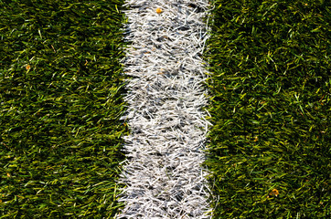 Artificial grass on football green field detail with white line