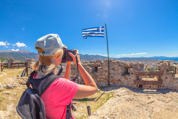 Traveler woman photographer with professional camera takes shot of Patra Castle ruins, Peloponnese, Greece. Caucasian female photographing outdoors. Europe travel concet. Flag of Greece on background