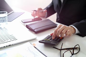businessman hand working with finances about cost and calculater and latop with mobile phone on withe desk in modern office