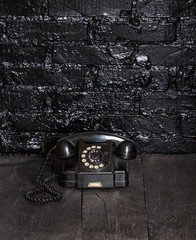 Black ancient phone on a black table