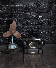 Black old phone and fan on a black table