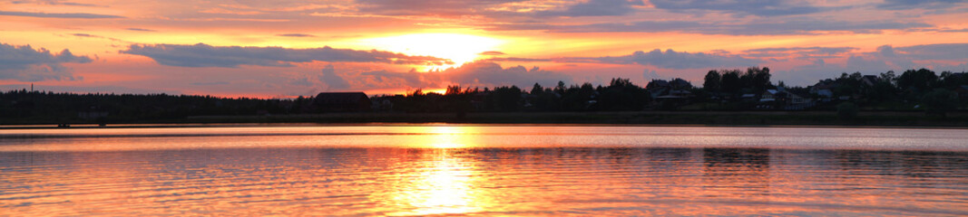 Panorama of the sunset overlooking the lake and the house and trees on the opposite coast.