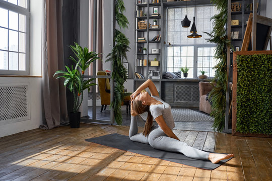 Woman practicing advanced yoga in the living room at home. A series of yoga poses