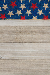 Red and blue stars burlap ribbon on weathered wood background