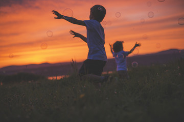 boys running to hit bubble on a sunset meadow