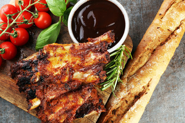 Spicy hot grilled spare ribs from a summer BBQ served with fresh tomatoes on an old vintage wooden cutting board