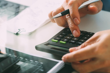 close up of businessman hand working with finances about cost and calculator and latop with mobile phone on withe desk in modern office