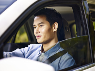 young asian man driving a car