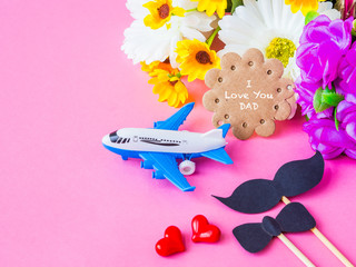 Father's day concept. I LOVE YOU DAD message with white and yellow flower, two red heart, black Mustache and bairplane model on pink background