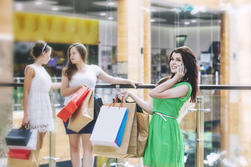 Women friends while shopping with packages and shopping