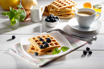 Belgian waffles for breakfast with a cup of coffee on a white table