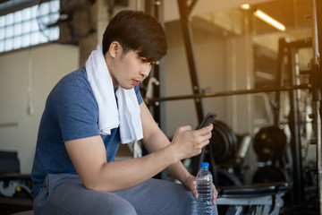 Young Asian man using mobile phone in the fitness gym after work out training