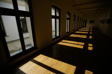 Window frames cast shadows on the floor of a wide empty room
