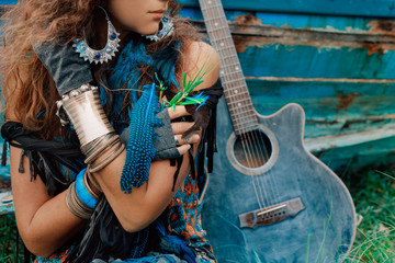 attractive gypsy girl close up portrait with a guitar leaning against the boat at background
