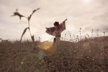Beautiful boho woman wearing poncho on green field at sunset
