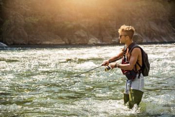 Young handsome male tourist standing and fishing in river in sunny day with rod