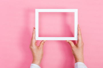 Person holding up a white frame